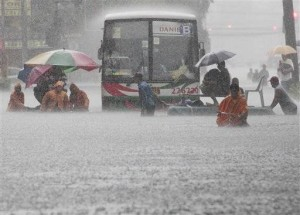Aug. 20, 2013 file photo, office workers cross a flooded street using makeshift floats during heavy rain at the financial district of Makati, south of Manila, Philippines.AP/Aaron Favila