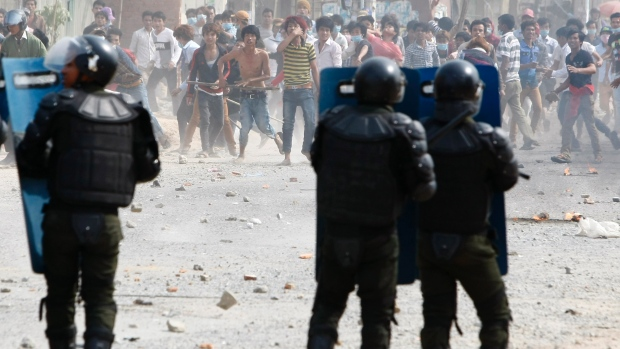 Cambodia garment workers throw stones at riot police during a strike near a factory on the Stung Meanchey complex on the outskirts of Phnom Penh on Jan. 3, 2014. At least three people were killed when police opened fire to break up a protest by striking garment workers demanding a doubling of the minimum wage, police and human rights workers said. Cambodia garment workers throw stones at riot police during a strike near a factory on the Stung Meanchey complex on the outskirts of Phnom Penh on Jan. 3, 2014. At least three people were killed when police opened fire to break up a protest by striking garment workers demanding a doubling of the minimum wage, police and human rights workers said. (Heng Smith/Associated Press)