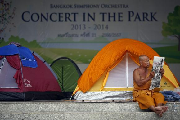 A Buddhist monk reads newspapers inside Lumpini Park where anti-government protesters have set up their tents in Bangkok