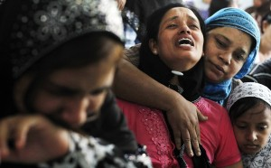 Tin Tin Kyaw (centre) cries near the body of her husband Soe Min, a 51-year-old man who was killed in the riot, at a mosque in Mandalay. Photo: Reuters
