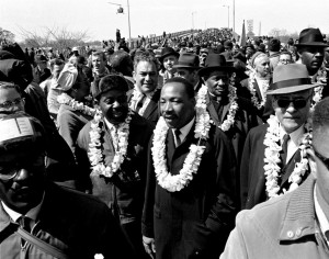 March 21, 1965 file photo, Martin Luther King Jr. and civil rights marchers cross the Edmund Pettus Bridge in Selma, Ala., heading for the capital, Montgomery, during a five-day, 50-mile walk to protest voting laws.  (AP Photo/File)